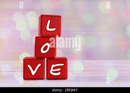 Love spelled in red wooden blocks on festive background - Stock Photo