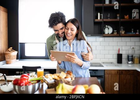 Beautiful couple in the kitchen while cooking.