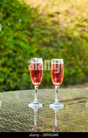 Pink champagne in two flute glasses side by side on a glass table top in a garden - Stock Photo