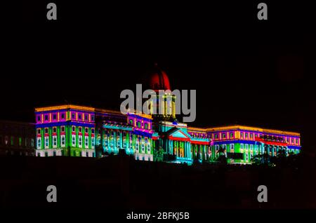 Hungarian National Gallery building lit in vibrant colours at night, the architecture standing out in the dark at Budapest, Hungary - Stock Photo
