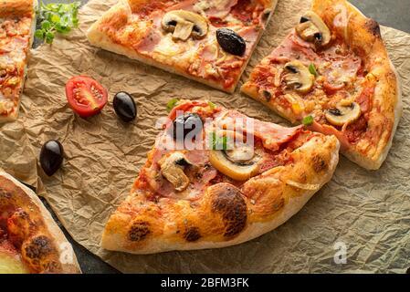 Pizza slices served with mozzarella cheese, ham, mushrooms and tomato sauce. Slice of fresh italian classic original pizza - Stock Photo