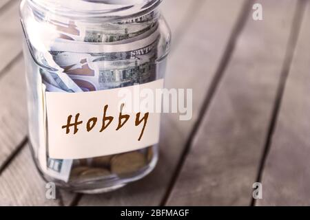Savings in glass bank on wooden background - Stock Photo