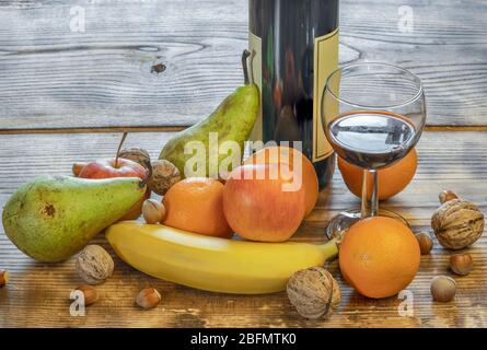 A glass and a bottle of fruit wine and mixed fruit next to the table - Stock Photo