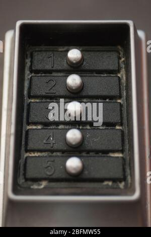 Close up of a dirty door lock metal keypad. Macro view of the buttons and digits of a doorlock keypad.