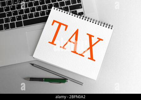 Tax Concept. Notebook on laptop keyboard, on light background - Stock Photo