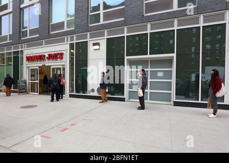 People wearing masks and social distancing as they queue to enter a supermarket during coronavirus covid 19. New York, NY, April 17, 2020. - Stock Photo