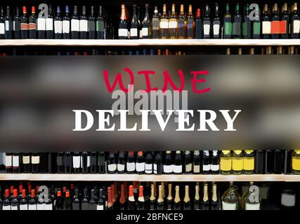 Text WINE DELIVERY on wine bottles background - Stock Photo