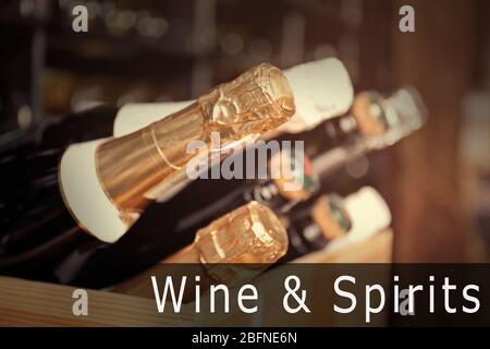 Bottles of different wine in wooden crate, closeup. Text WINE AND SPIRITS on background - Stock Photo