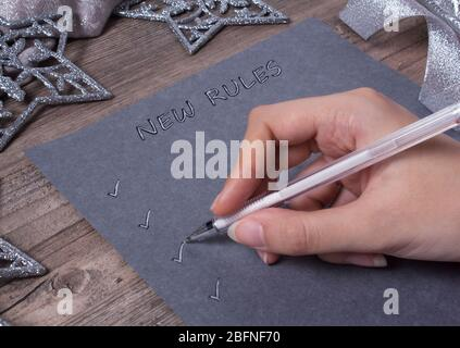 A person writes words on grey paper. New year, new rules. Motivation, plan, schedule, task, new life. Christmas, holiday. Snowflakes and Christmas toy