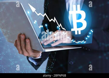Bitcoin rate and businessman using laptop on color background - Stock Photo