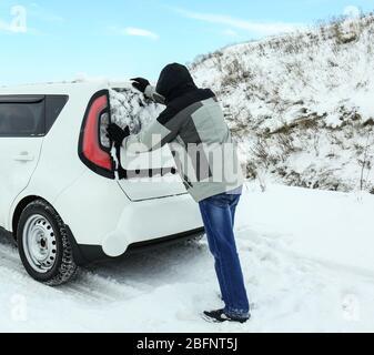 Man pushing car stuck in snowdrift on winter road - Stock Photo