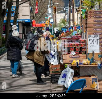 Customers line up at a fruit stand in the Chelsea neighborhood of New York on Tuesday, April 14, 2020.  (© Richard B. Levine) - Stock Photo