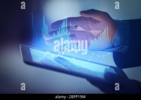 Businessman working with tablet and virtual graphs, closeup. Financial trading concept - Stock Photo