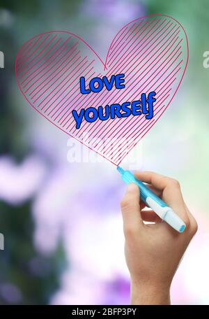 Male hand with marker writing Love yourself on natural background - Stock Photo