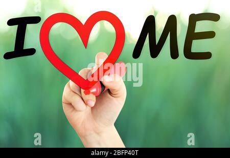 Love yourself concept. Hand writing I Love Me on transparent whiteboard on natural background - Stock Photo