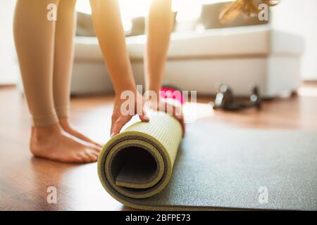 Young woman doing yoga workout in room during quarantine. Cut low view of barefeet girl rolling up yoga mat after finishing stretching or exercising.