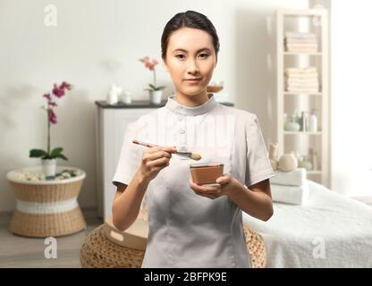 Young Asian beautician in spa salon at work - Stock Photo
