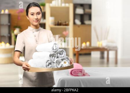 Young Asian masseur holding tray with towels in spa salon - Stock Photo