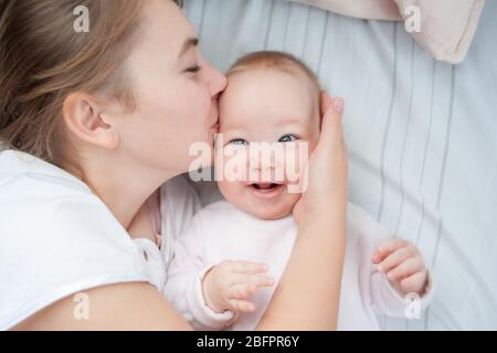 Mother kissing her infant baby in bed. Happy mother kisses baby lying on the bed. Beautiful smiling girl lying on her back. Top view. Flat Lay Stock Photo