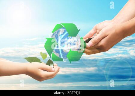 Mother and child hands with globe and sign of recycling on sky background. Ecology and environment conservation - Stock Photo
