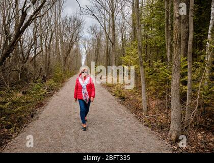 A woman wearing a bright red coat walks alone down a forest trail during the Covid-19 pandemic.