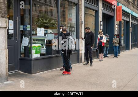 New York, NY, USA. April 19, 2020. People practicing social distancing as a result of the Coronavirus upbreak while on line outside of a butcher shop - Stock Photo