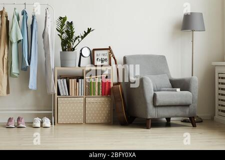 Full length view at studio apartment interior with minimal design, focus on comfy grey armchair and clothes rack against white wall, copy space - Stock Photo
