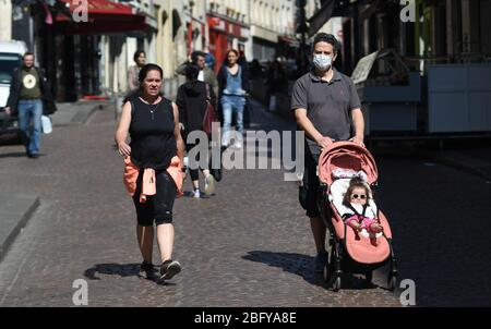 *** STRICTLY NO SALES TO FRENCH MEDIA OR PUBLISHERS - RIGHTS RESERVED *** April 05, 2020 - Paris, France: A family take their child out in rue Mouffetard three weeks into a lockdown against the coronavirus outbreak. - Stock Photo