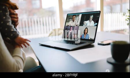 Businesspeople having a video call. Woman at home using a laptop to connect with her colleagues to discussing work. - Stock Photo