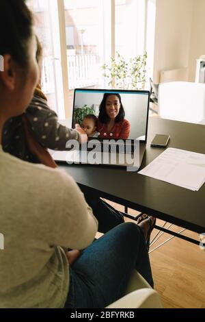 Woman sitting at table with her kid having a video call with a friend. Mother and son having video chat with family friends at home. - Stock Photo