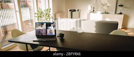 Laptop on table with a video call on the screen in living room. People using VoIP to connect together.