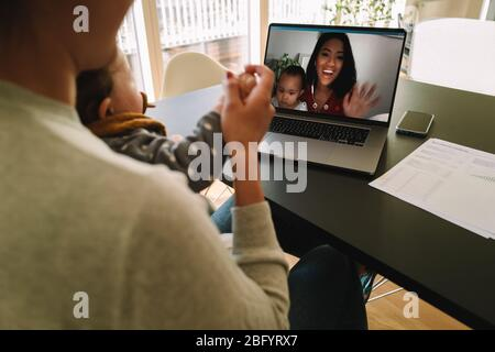 Woman using a laptop to connect with her sister during quarantine. Female friends with their kids having a video call on a laptop computer at home. - Stock Photo