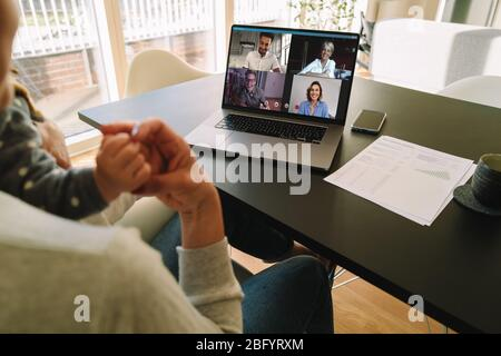 Woman with her child having video call with coworkers while working from home. Work from home mom. - Stock Photo