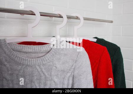 Clothes hang on hangers. Sweaters in red, green and melange colors. Fashion and style, showcase, store, concept. White brick wall, comfort and cleanin - Stock Photo