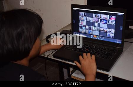 Indian student attending, watching, focusing, concentrating on school's live online classes or digital class during covid  or corona distant learning - Stock Photo