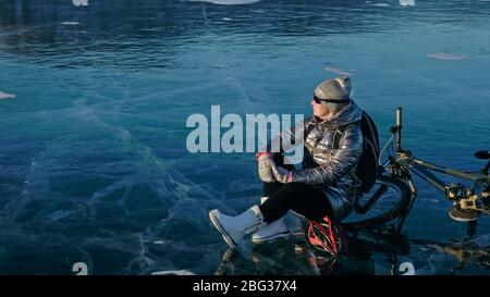 Woman sitting near her bike on ice. The girl cyclist stopped to - Stock Photo