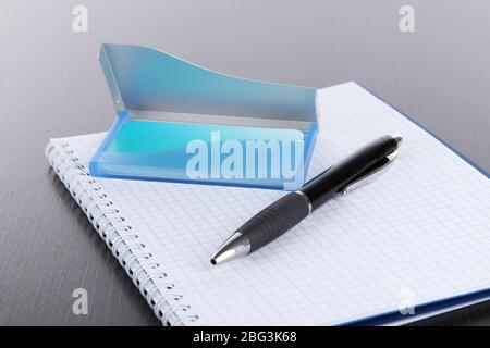 Blue business card holder, notebook and pen close-up