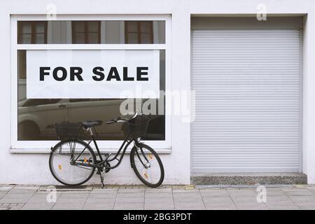 for sale sign in store window with bicycle parked outside - shop vacancy due to business closure - economy crisis and recession concept - Stock Photo