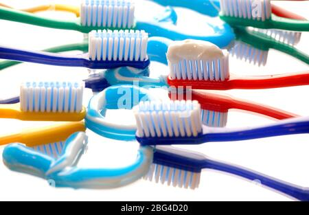 The word 'tooth' is written out using toothpaste on a mirrored surface, surrounded by multicouloured toothbrushes. - Stock Photo