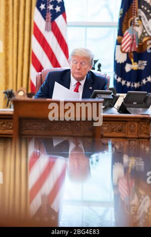 U.S. President Donald Trump talks on the speaker phone with Mexican President Andres Manuel Lopez Obrador in the Oval Office of the White House April 17, 2020 in Washington, DC. - Stock Photo