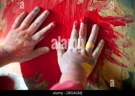 Toddler finger paints with red paint on canvas - Stock Photo