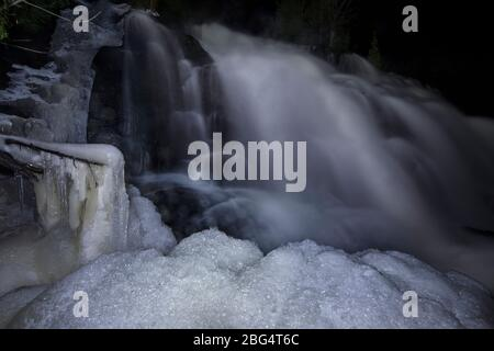 A frozen waterfall in kitch-iti-kipi state park in Michigan - Stock Photo