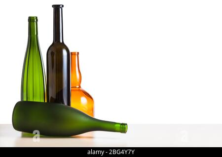 four various empty bottles on wooden table with cutout background - Stock Photo