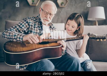 Photo of funny aged old grandpa little pretty granddaughter holding playing guitar teaching small princess bonding spend stay home quarantine useful - Stock Photo