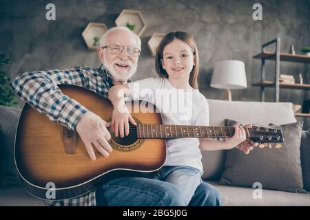 Photo of funny aged old grandpa little pretty granddaughter holding playing guitar teaching bonding duet spend time together stay home quarantine - Stock Photo