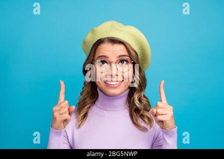 Portrait of positive cheerful girl promoter indicate ads promo point finger copyspace recommend suggest select wear trendy green violet headwear - Stock Photo