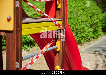 Children's playground in Berlin, Germany, which was closed due to the Covid-19 virus and the blocking of contact with a barrier tape. - Stock Photo