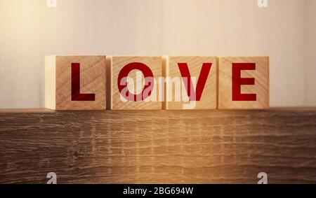 LOVE word from letter wooden blocks on wooden background. Relationship concept - Stock Photo