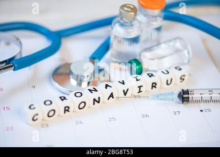 Coronavirus vaccine with syringe injection medication drug and stethoscope on calendar / Vaccine bottle for COVID-19 coronavirus spread influenza medi - Stock Photo
