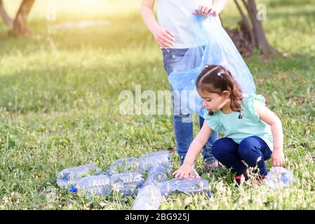 Cute little girls cleaning up plastic litter on grass. Children Volunteers cleaning up litter and putting plastic bottle into recycling bag. World Environment Day.